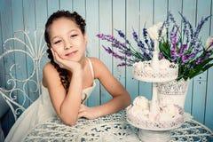 有甜点的女孩在桌上 免版税库存图片