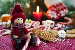 有甜点的木微笑的玩偶在与罐头的圣诞节背景 免版税库存照片