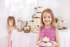 有甜点的逗人喜爱的小女孩 免版税库存照片