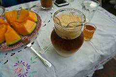 有甜瓜瓜切片,并且一杯冰冻咖啡拿铁在桌上 免版税库存图片