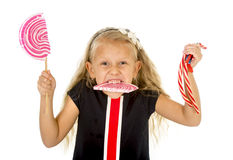 有甜蓝眼睛和长的金发的美丽的矮小的女孩吃巨大的棒棒糖螺旋糖果的 免版税库存照片