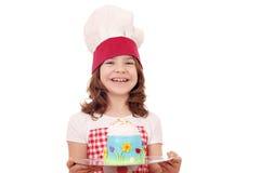 有甜蛋糕的小女孩厨师 免版税库存图片