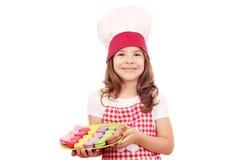 有甜macarons的小女孩厨师 库存图片