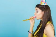 有生日帽子和口哨的年轻可爱的微笑的妇女在蓝色背景 庆祝和党 免版税库存照片