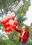 有生日气球的一个十几岁的女孩 免版税库存图片
