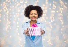有生日礼物箱子的愉快的非洲妇女 图库摄影