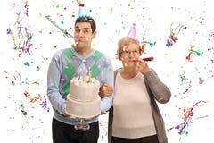 有生日蛋糕和成熟妇女吹的党垫铁的年轻人 库存照片