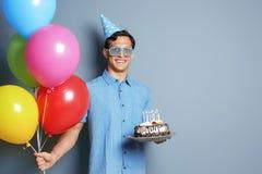 有生日蛋糕的年轻在颜色背景的人和气球 免版税库存图片