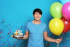 有生日蛋糕的年轻在颜色背景的人和气球 库存照片