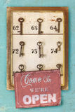 有生锈的旅馆钥匙和开放标志的小葡萄酒内阁 库存照片