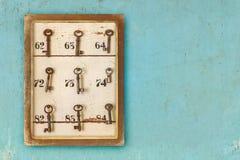 有生锈的旅馆钥匙和房间号的小葡萄酒内阁 免版税图库摄影