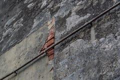 有生锈的管子的水泥织地不很细墙壁 免版税库存图片
