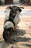 有生锈的组分的老被放弃的摩托车在尘土 库存图片