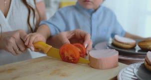 有用刀子一起切开的一个小孩子的一个年轻母亲一个自创汉堡的一个蕃茄 一起健康食品厨师 影视素材