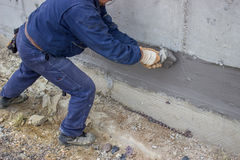 有用刷涂敷的与氢结合的绝缘材料的2建筑工人 库存图片