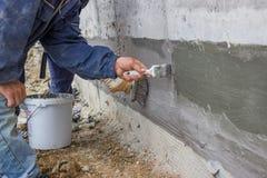 有用刷涂敷的与氢结合的绝缘材料的2建筑工人 库存照片