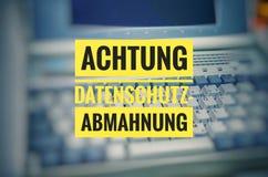 有用德语的在英国关注保密性警告的Achtung Datenschutz-Abmahnung膝上型计算机 免版税库存照片