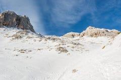 有用早期的雪报道的峰顶的壮观的冬天山全景 免版税库存照片