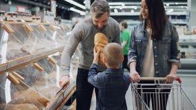 有用的儿子帮助他的父母买面包,父亲是打开容器,并且男孩采取大面包并且嗅到它 影视素材