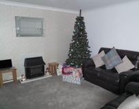 有用礼物装饰的圣诞树的一个现代休息室在i 免版税库存图片