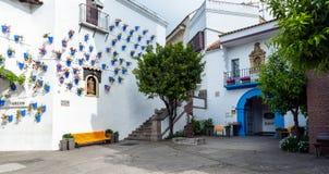 有用美丽的蓝色花盆装饰的白色墙壁的传统西班牙村庄 免版税库存照片
