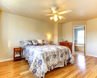 有用花装饰的卧具和硬木地板的简单的卧室。 库存照片