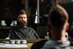 有用黑海角盖的胡子的人在镜子前面的美发师椅子坐 有胡子的行家检查结果的 库存图片