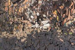 有由与被变形的反射的残破的镜子片断做的肮脏的马赛克的崩裂的水泥墙壁在他们 免版税库存图片