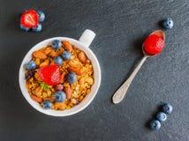 有由燕麦剥落做的格兰诺拉麦片的早餐碗、干果子和坚果和新鲜的蓝莓和草莓 图库摄影