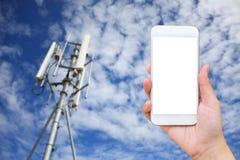 有电信塔的手举行流动智能手机 免版税库存照片