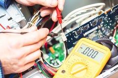 有电压表的技术员手在计算机主板上 计算机概念修理  定调子与选择聚焦 图库摄影