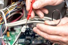 有电压表的技术员手在计算机主板上 计算机概念修理  定调子与选择聚焦 免版税库存图片