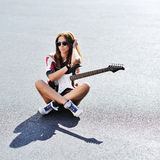 有电吉他的可爱的年轻时髦的妇女 免版税库存图片
