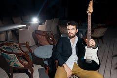 有电吉他的时髦的有胡子的人; 免版税库存照片