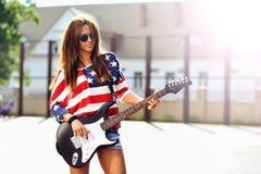 有电吉他的年轻美丽的女孩 室外时尚portr 免版税库存照片