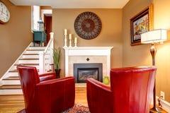 有电壁炉和典雅的红色椅子的明亮的家庭娱乐室 图库摄影