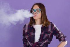 有电子香烟的年轻俏丽的女孩 库存图片