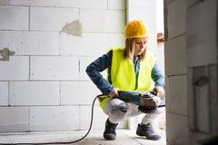有电工具的少妇工作者在建造场所 免版税库存图片