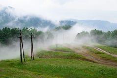 有电柱子的山雾盖子明亮的新鲜的草甸 图库摄影