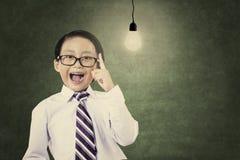 有电灯泡的天才男小学生 库存照片