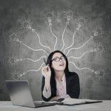 有电灯泡的女实业家在黑板 免版税库存图片