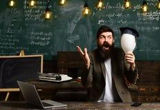 有电灯泡的有胡子的人在教室有想法 有电灯泡的有胡子的科学家在黑板,启示 免版税库存图片