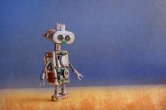 有电灯泡的机器人飞碟外籍人玩具注视,金属春天手,蓝色黄色未来派背景 复制空间 库存图片