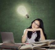 有电灯泡的聪明的少年学生 库存图片