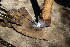 有电烙术的焊接的老打破的锄 库存照片