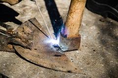 有电烙术的焊接的老打破的锄 免版税库存照片