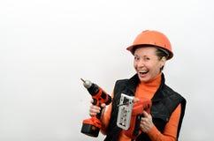 有电螺丝刀和工具的快乐的微笑的妇女建筑工人在苦恼的手上看见了 库存照片