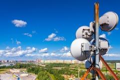有电视天线、卫星盘和移动运营商微波天线的通讯工具反对蓝天的与克洛 图库摄影