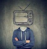 有电视的上瘾的人而不是他的在灰色背景的头 免版税图库摄影