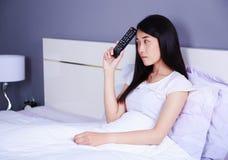 有电视的妇女遥控在床上在卧室 库存图片